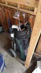Two sets of golf clubs with hand carts