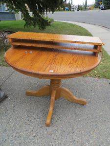 Solid oak round pedestal dining table with 2 leaves