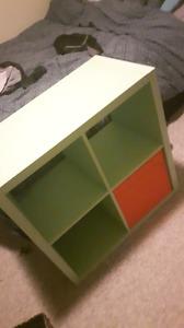 Mint green KALLAX cube shelf with 4 orange baskets