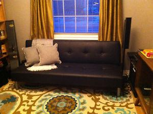 Black faux-leather futon for sale. Can deliver in St.