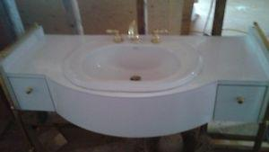 vanity with gold trim and matching mirror and matching taps